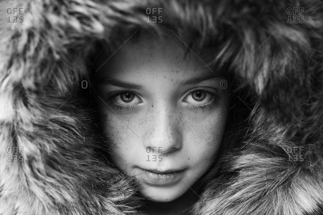 Close-up portrait of young child in fur hood