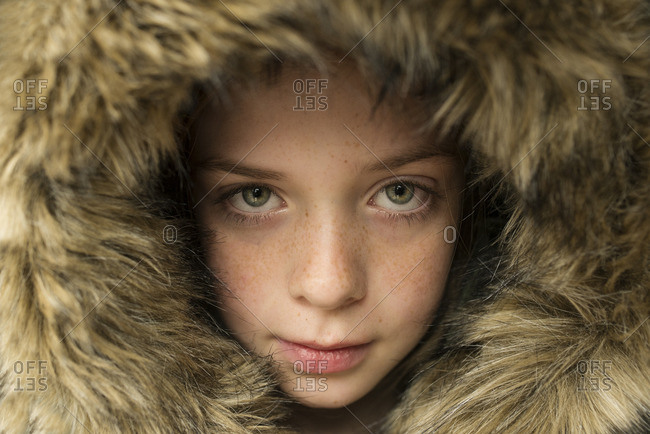 Portrait of a green-eyed girl in fur hood