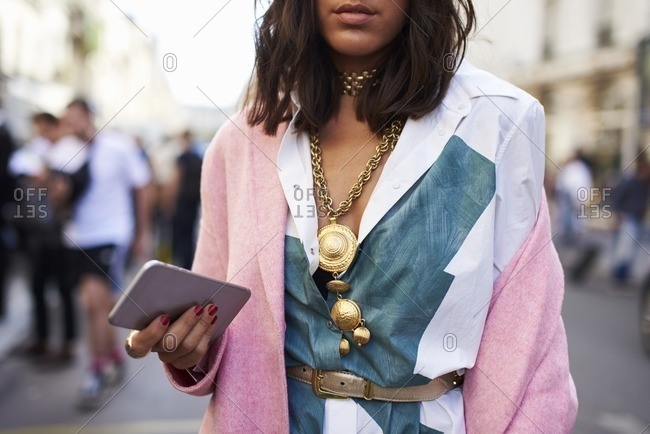 Woman in pink coat and necklace holds phone in street