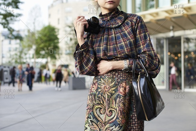 Woman in plaid top and floral panel skirt holding camera