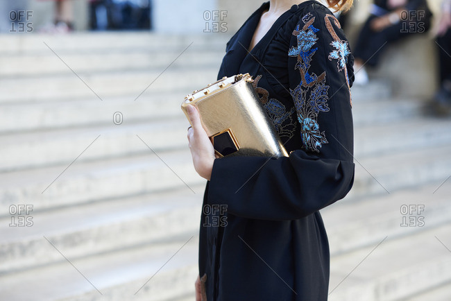 Woman in dress with embroidery holding gold bag