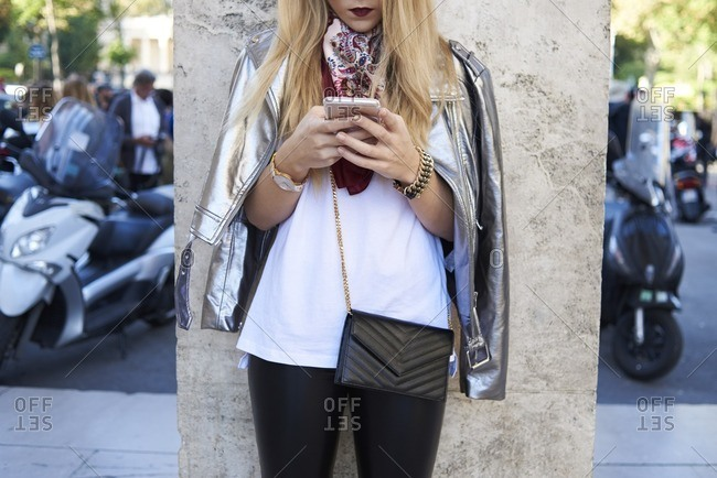 Woman using smartphone, silver jacket over shoulders