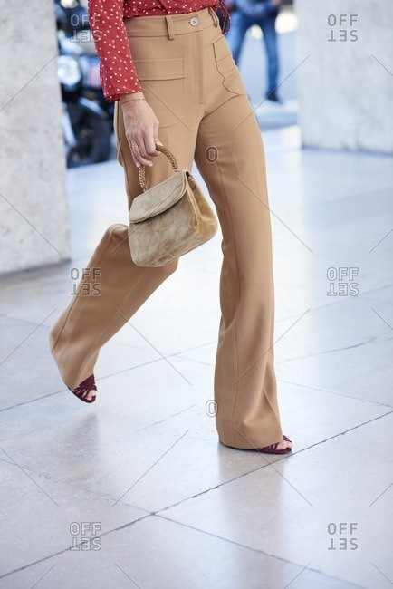 Woman walking in fawn flares and red blouse