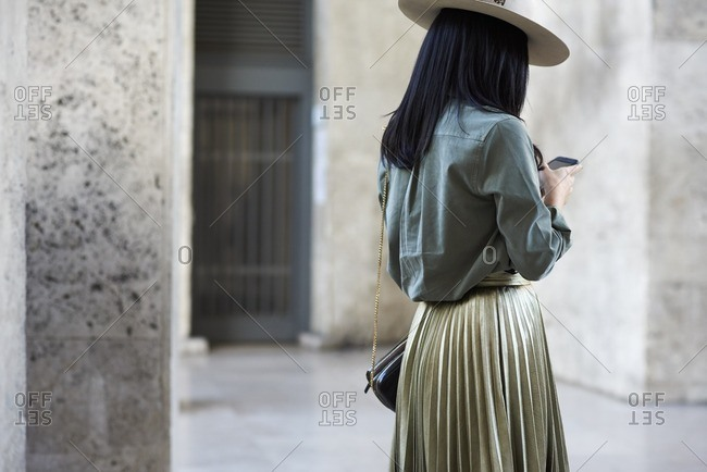 Woman in gold pleated skirt and hat using phone