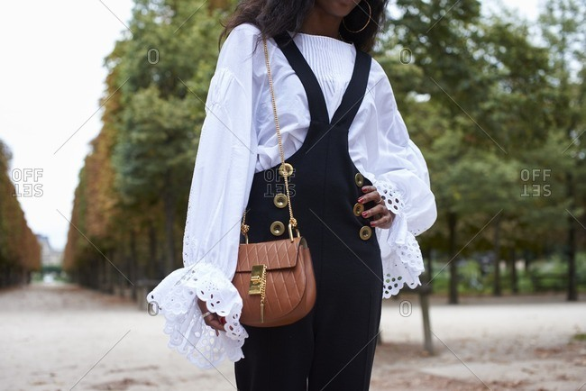 Woman in dungarees and a gypsy blouse with bag
