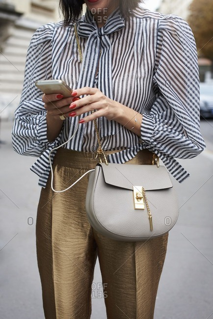 Woman in striped blouse using phone in street