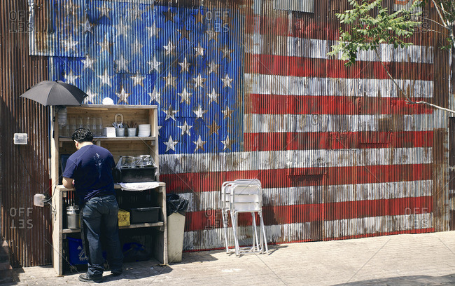 Person standing in front of shelves with kitchen supplies against building with American flag on corrugated metal