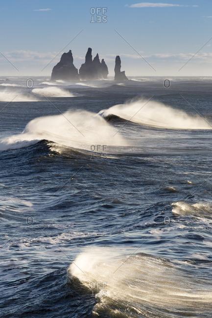 Waves moving to Reynisfjara beach, with the Reynisdrangar sea stacks on the horizon,Vik,southern Iceland,Europe