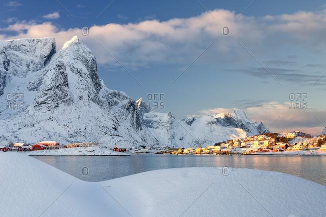 Sun on fishing village surrounded by snowy peaks and frozen sea Kvalvika Andøya Reine Nordland Lofoten Islands Norway Europe