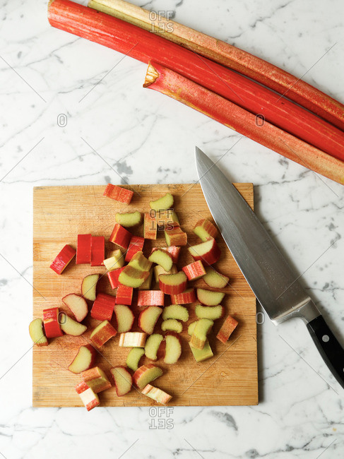 Rhubarb sliced on a cutting board with a knife