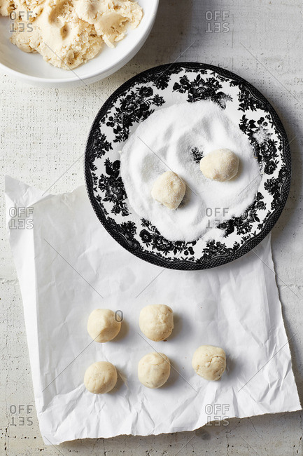 Two dough balls being rolled in sugar for anise sugar cookies