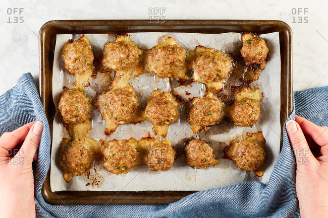 Hands holding baking pan with fresh baked meatballs
