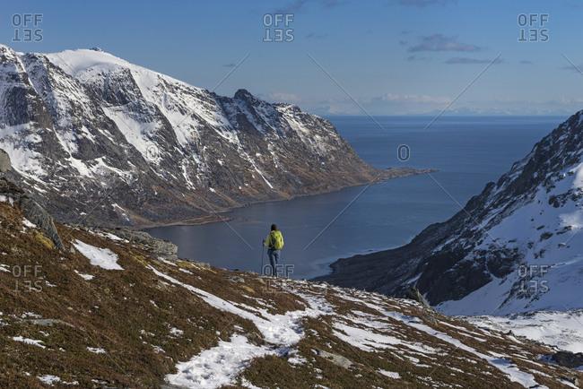 Female Hiker Descending Rocky Ridge Towards Skjelfjorden In Lofoten Islands, Norway