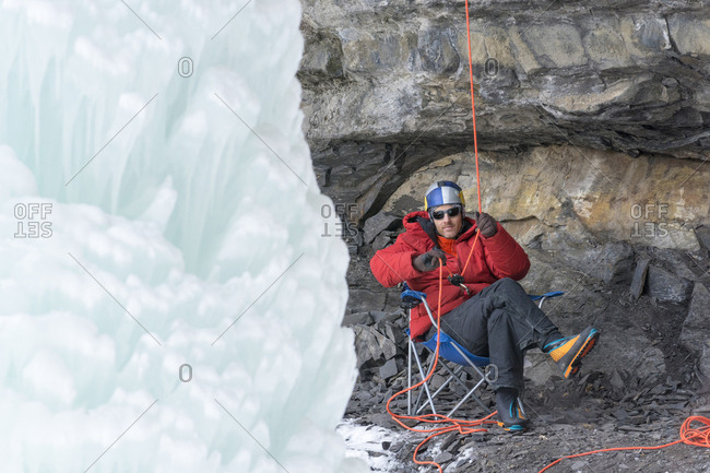 Will Gadd sitting in a chair belaying while ice climbing in Vail, Colorado