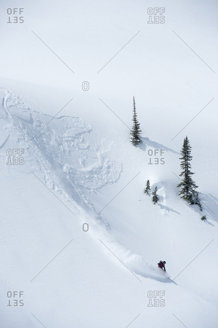 A snowboarding doing a slash in fresh powder in the Canadian backcountry