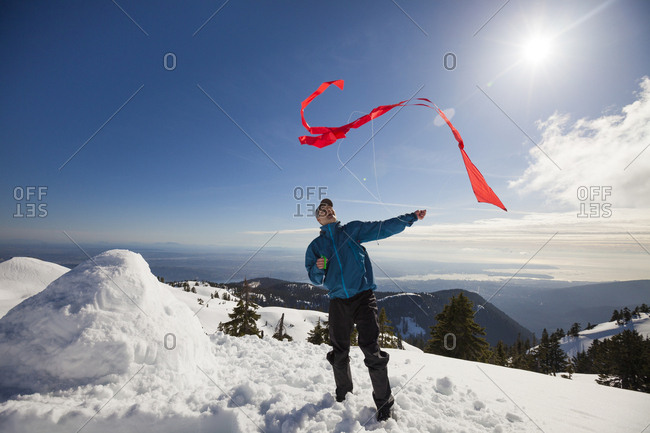 A hiker attempts to fly  a kite on the top of a snow covered mountain.