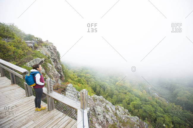 An adult woman stopped to read information at the Lake of the Clouds overlook in the Porcupine Mountains Wilderness State Park in the Upper Peninsula of Michigan
