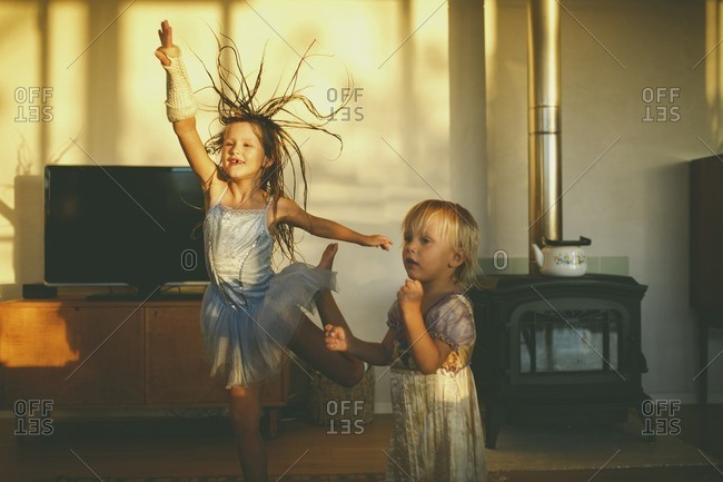A girl dancing with plastered arm and little brother wearing dress