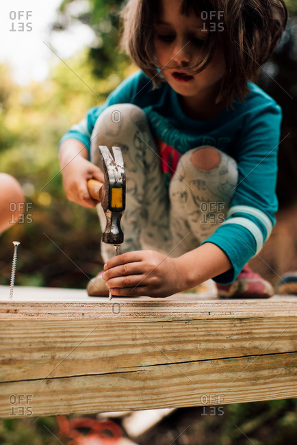 Little girl hammering a screw into wood