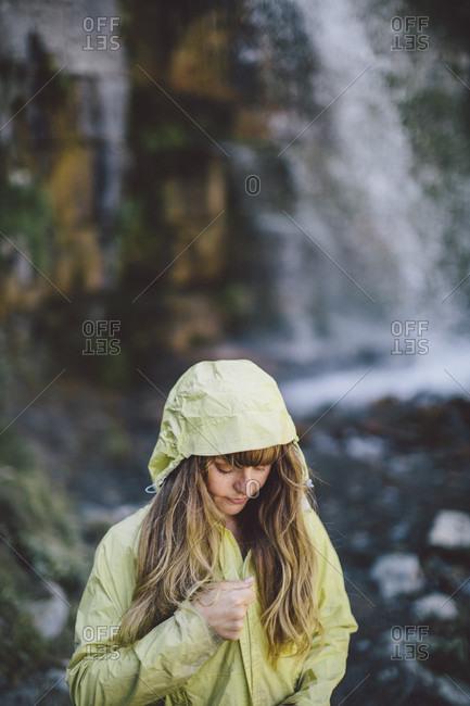 Young Woman Zipping A Rainy Jacket Near A Waterfall