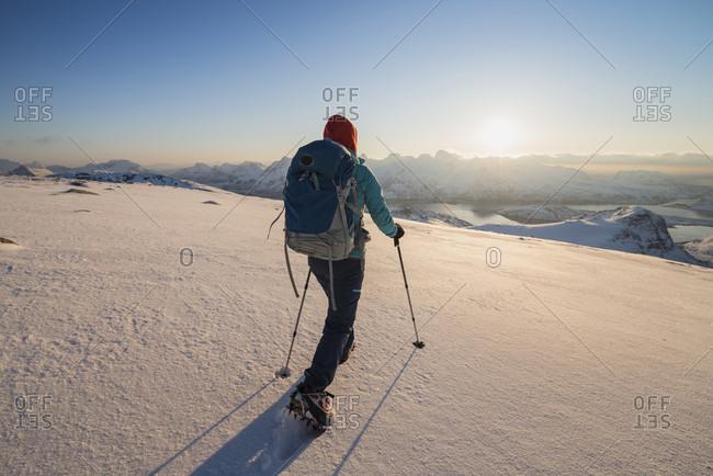 Female Hiker Descending Snowy Hillside From Summit Or Ryten, Lofoten Islands, Norway