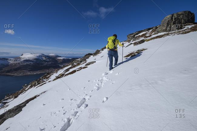Female Hiker Hiking On Snow Near Summit Of Volandstind, Flakstad, Lofoten Islands, Norway