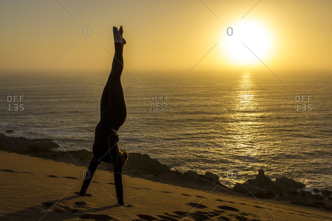 Woman Doing Handstand In The Sand During Sunset