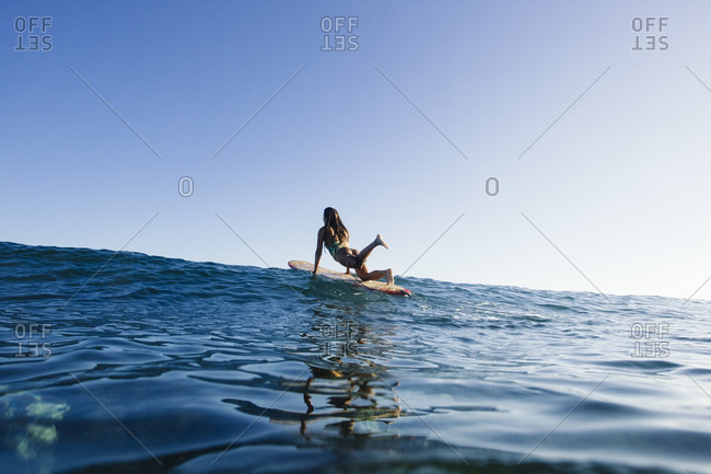 A Surfer Girl Longboarding On A High Wave In Spain