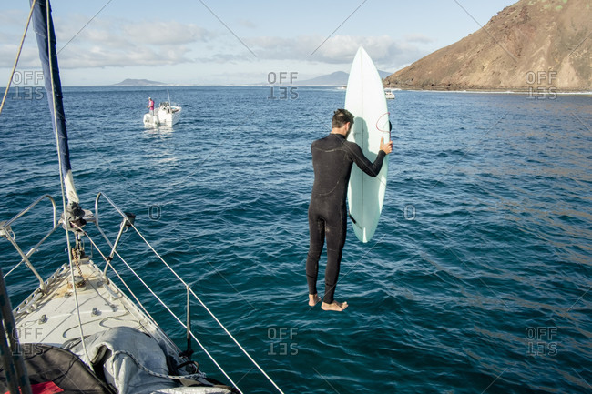 Man Jumping With His Surfboard In Water
