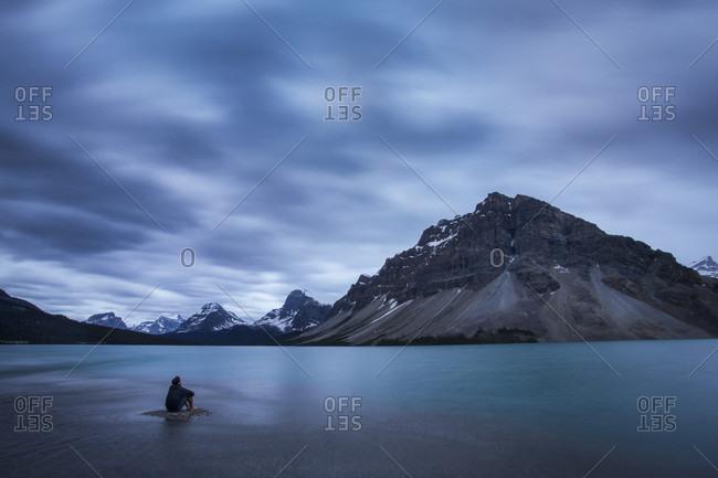 Man Sitting At Bow Lake In Canada