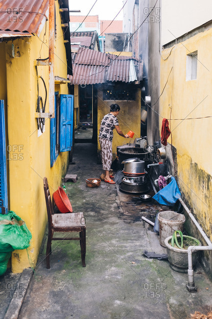 Woman washing dishes in an alleyway