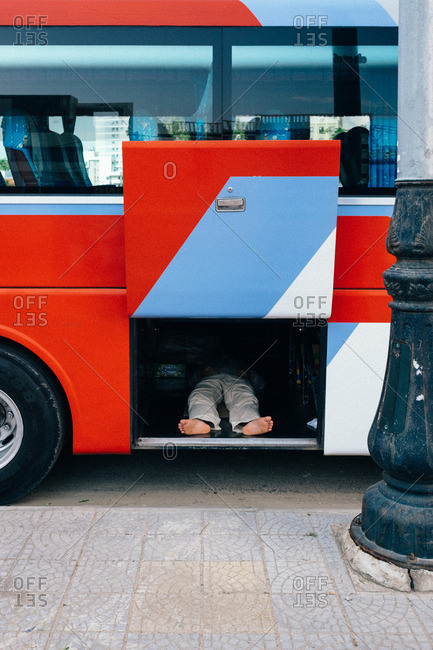Man lying in the storage area under a bus