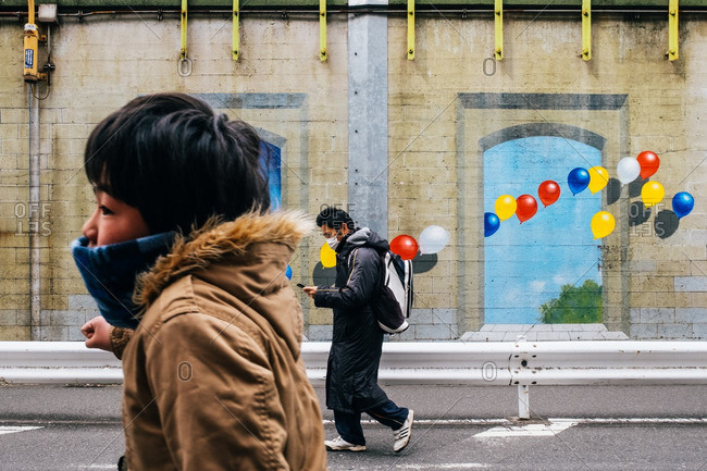 Tokyo, Japan - March 12, 2016: Two boys walking by a building with colorful balloons painted on the side