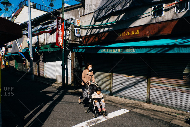 Tokyo, Japan - March 14, 2016: Woman pushing baby in a stroller