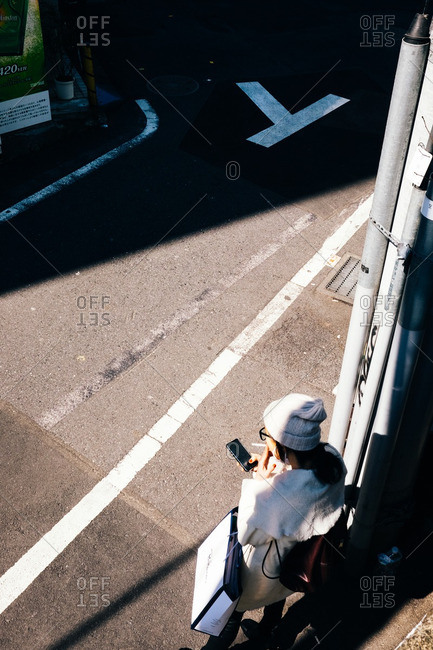 Tokyo, Japan - March 15, 2016: High angle view of a woman smoking a cigarette while using her cell phone outdoors