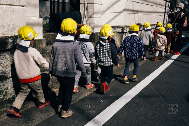 Tokyo, Japan - March 16, 2016: Children wearing yellow hats walking in a line together