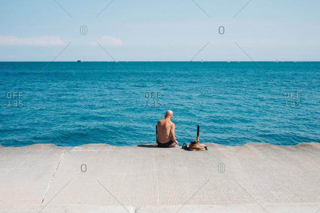 Shirtless man sitting on the shores of Lake Michigan