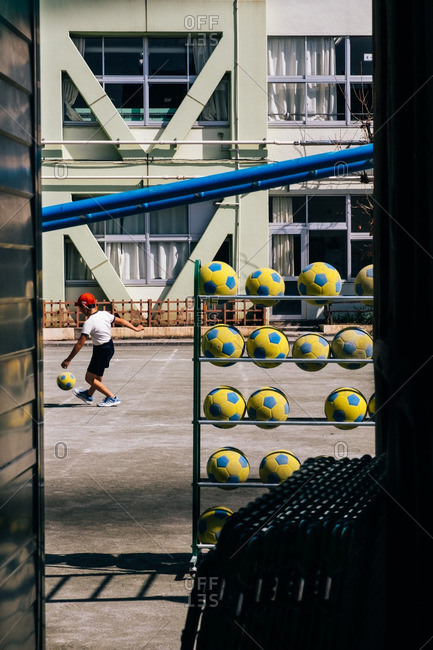 Tokyo, Japan - March 17, 2016: Child playing soccer in Tokyo