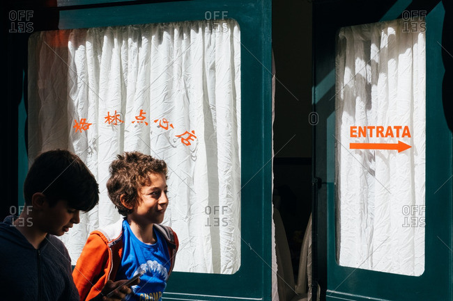 Milan, Italy - April 19, 2016: Boys walking by a shop in Chinatown, Milan, Italy