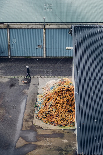 August 28, 2016: Person walking dog beside building with large pile of rope outside