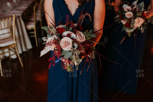 Bridesmaid holding bouquet of flowers on wedding day
