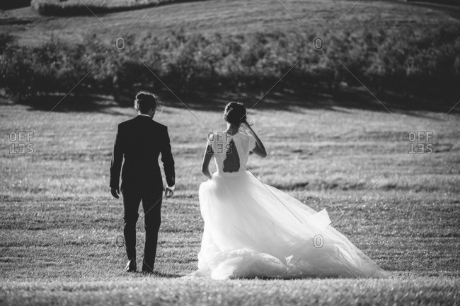 Bride and groom walking side by side through a meadow