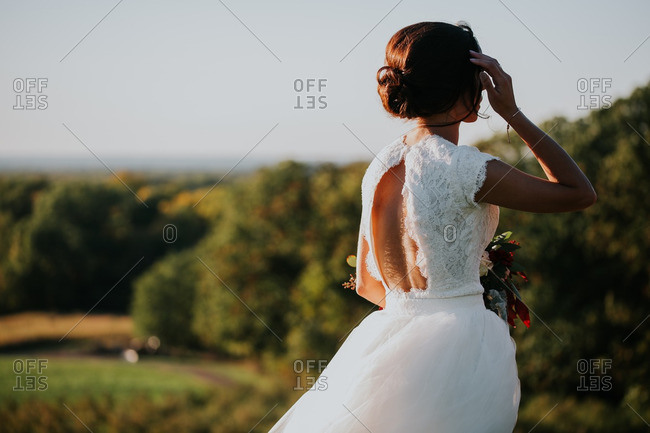 Bride looking out over a scenic vista on her wedding day