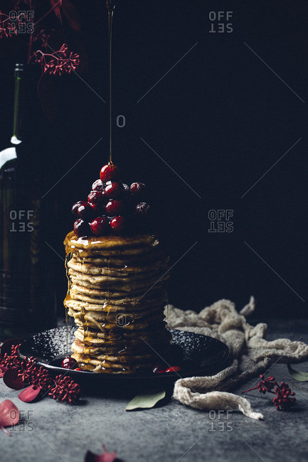 Pouring syrup on cranberry topped pancakes