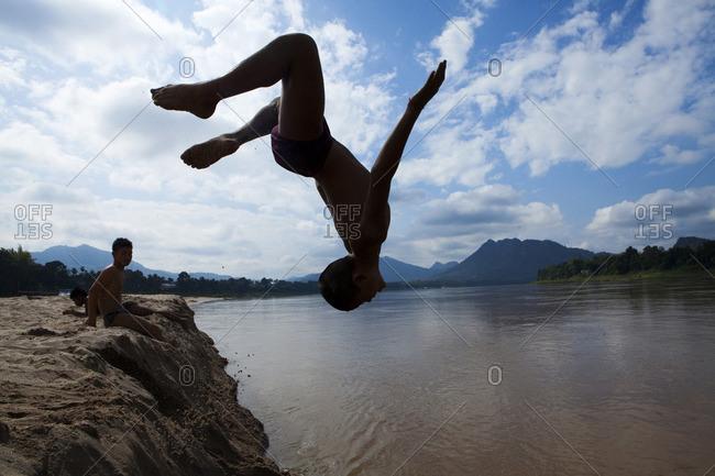 Luang Prabang, Luang Prabang, Laos - December 21, 2010: Silhouette of boy jumping into river