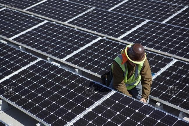 Worker examining solar panels outdoors