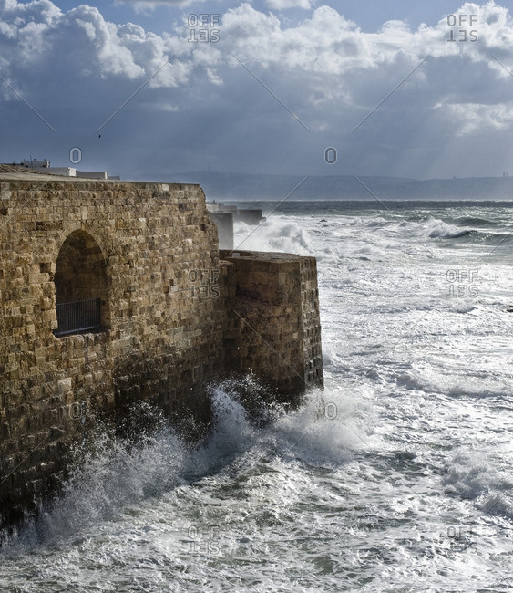 Waves breaking against ancient walls during a storm