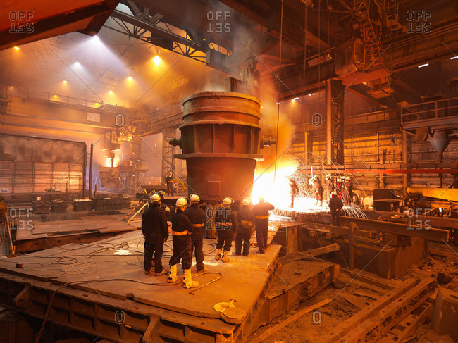 Steel Workers With Ladle And Sparks