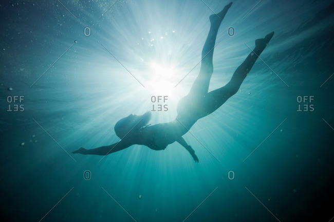 Silhouette of a girl underwater