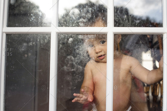 Toddler at a window looking out